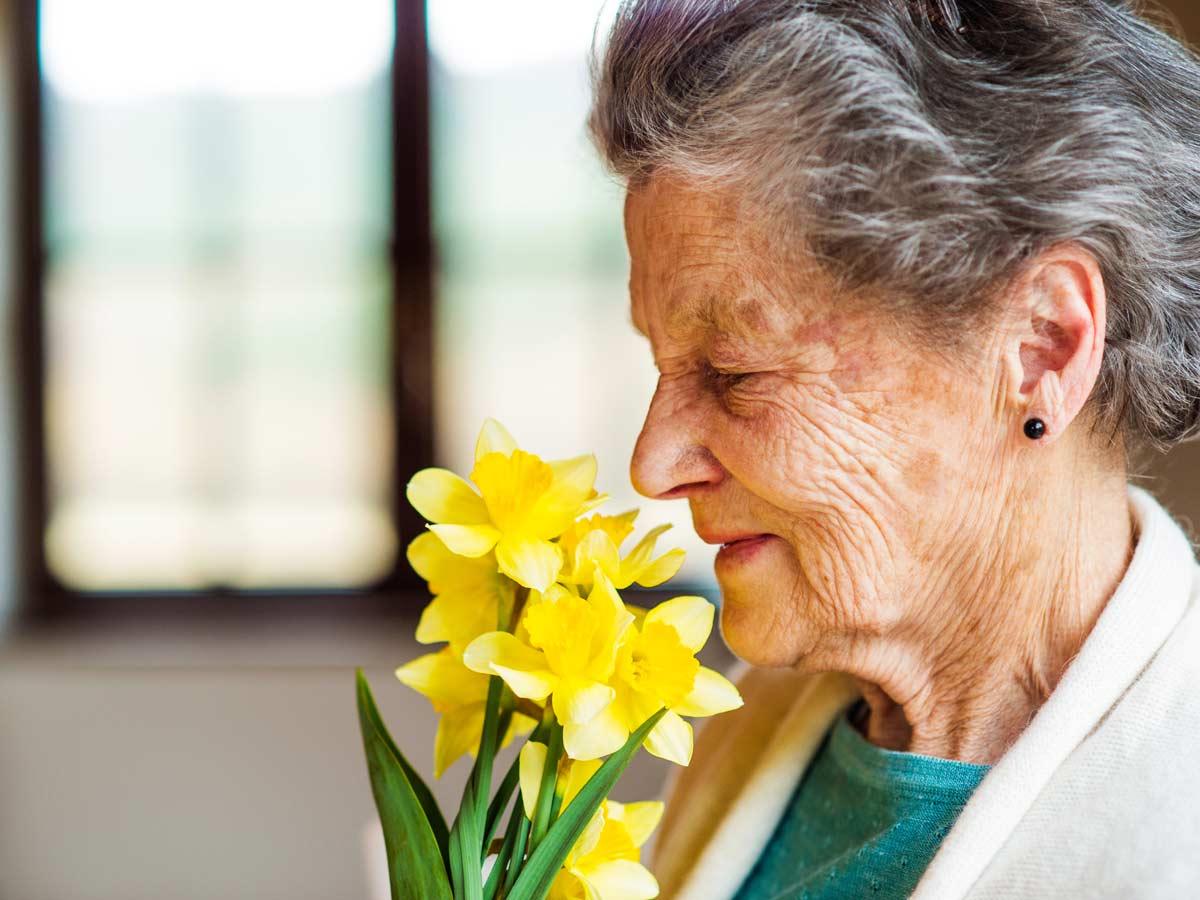 Vieille femme qui sent un bouquet de fleurs