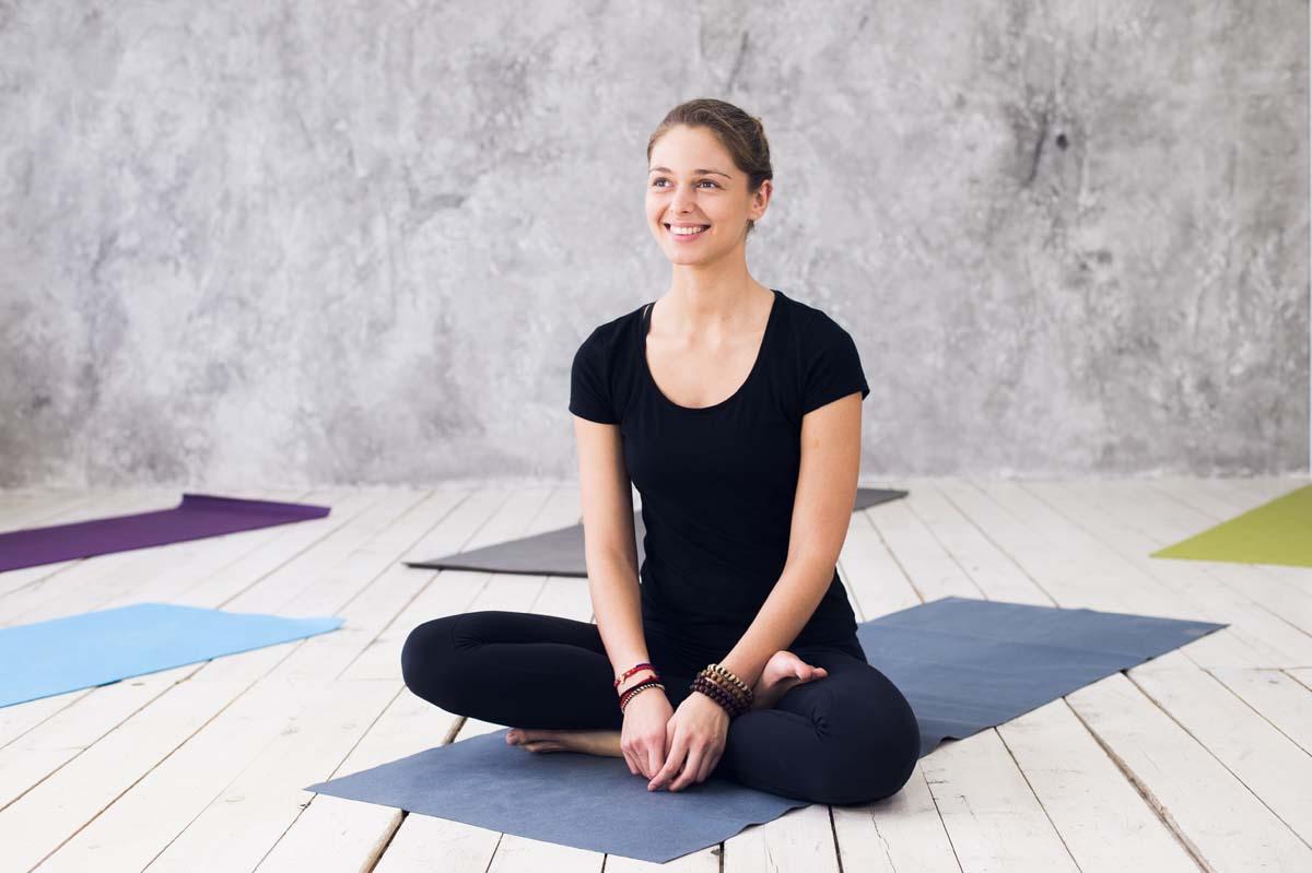 Image d'une jeune femme souriante en position de Yoga.