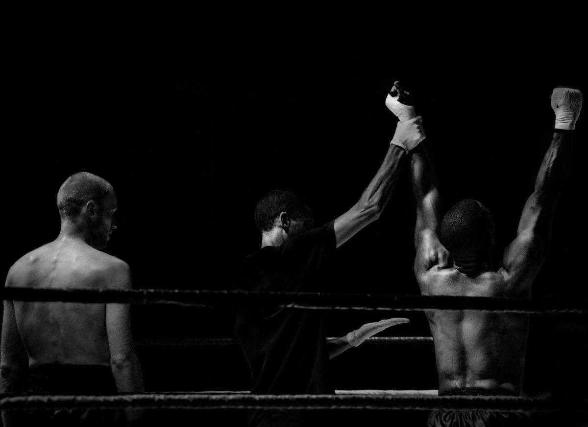 Une photo en noir et blanc d'un ring de boxe où un boxeur est annoncé vainqueur