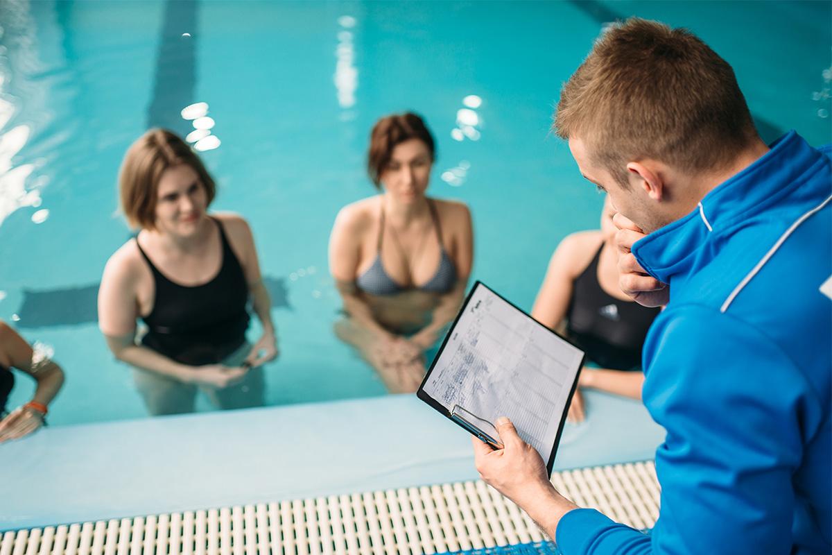 Kinésiologue effectuant un programme d'entrainement à des personnes dans une piscine.