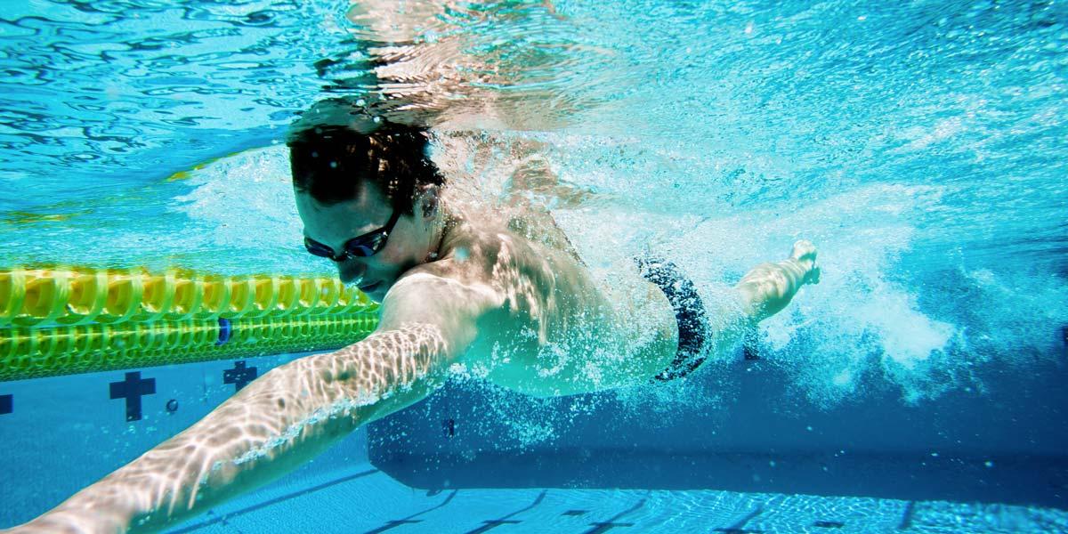 Homme nageant à la piscine