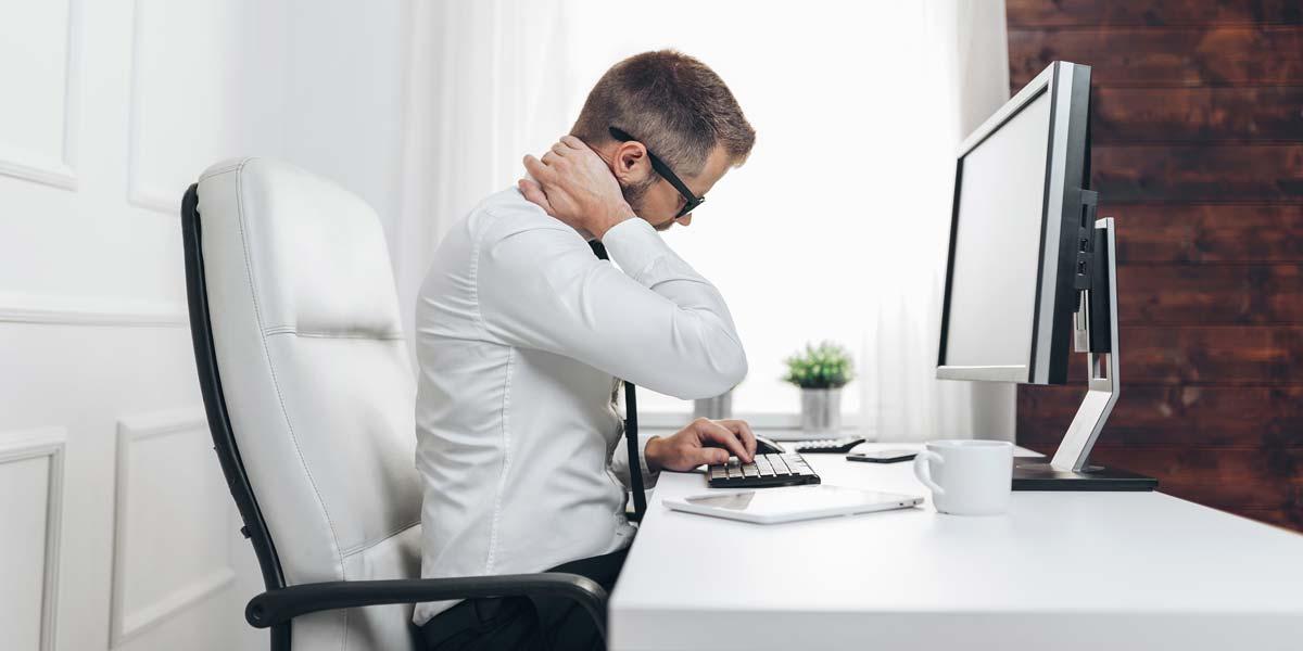 Homme assis à son bureau se tenant le cou dû à des douleurs