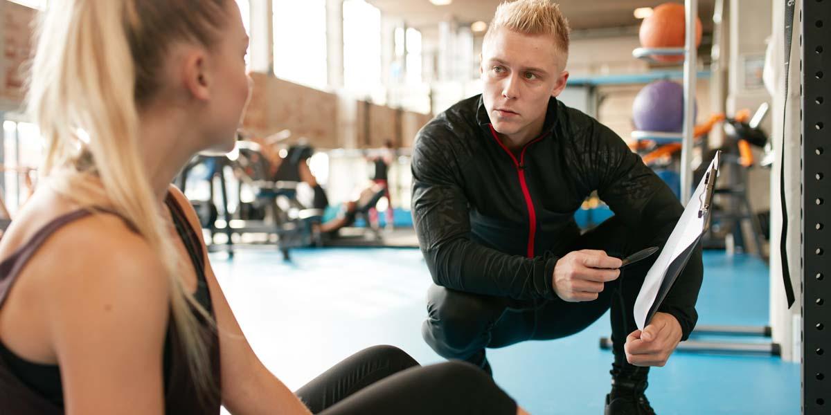 Un kinésiologue parle avec une cliente dans une salle d'entrainement
