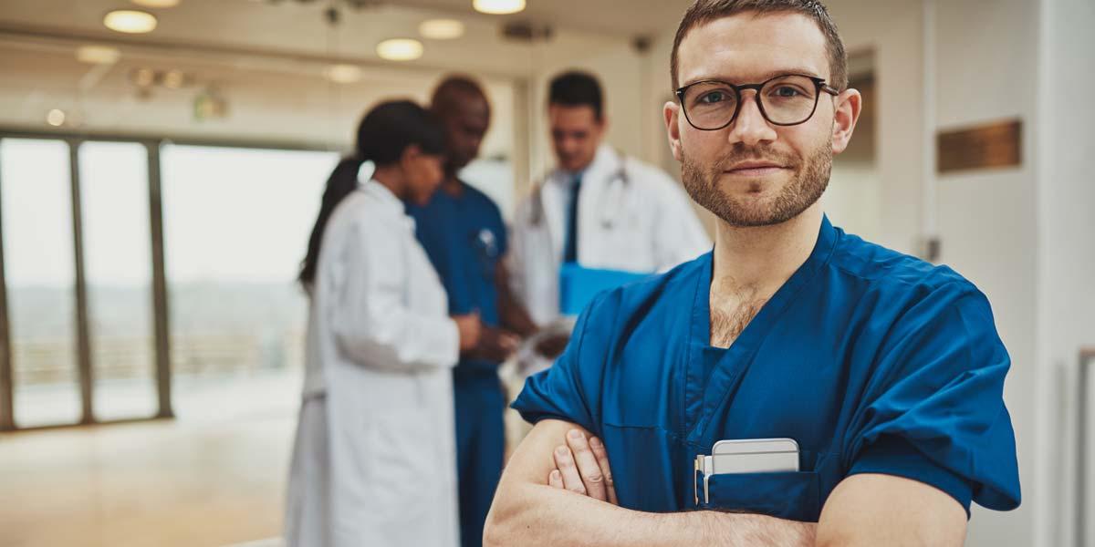 Un professionnel de la santé se tenant les bras croisés devant trois autres spécialistes.