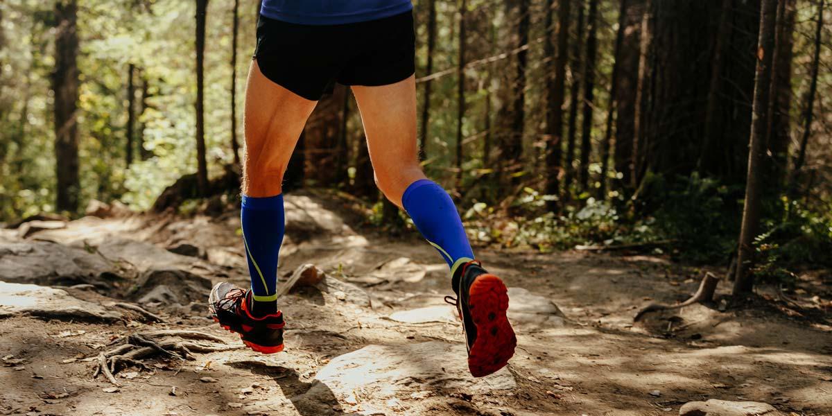 Homme courant dans la forêt avec ses bas de sport