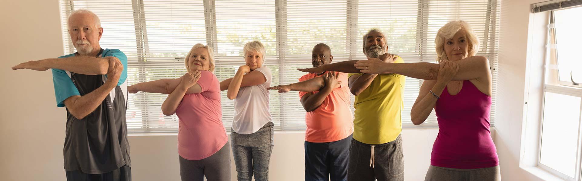 6 aînés à la salle de sport s'étirant le bras tous ensemble