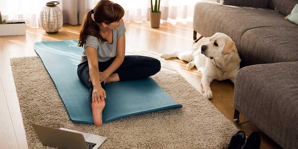 femme faisant de l'exercice à la maison à côté de son chien